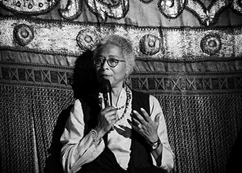 Black and white photograph of Alice Walker speaking with a microphone.